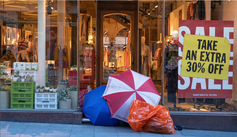a store front with sale signs and umbrella, black friday sale, ethical fashion, sustainable fashion, why we opt out of black friday