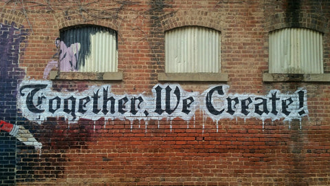 "Street art reading ""together we create"""