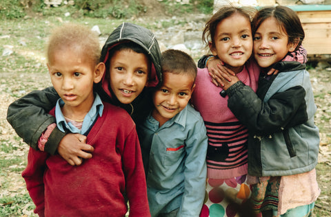Children in a group smiling. Goods for Good send valuable items to refugees, displaced communities and vulnerble people around the world.