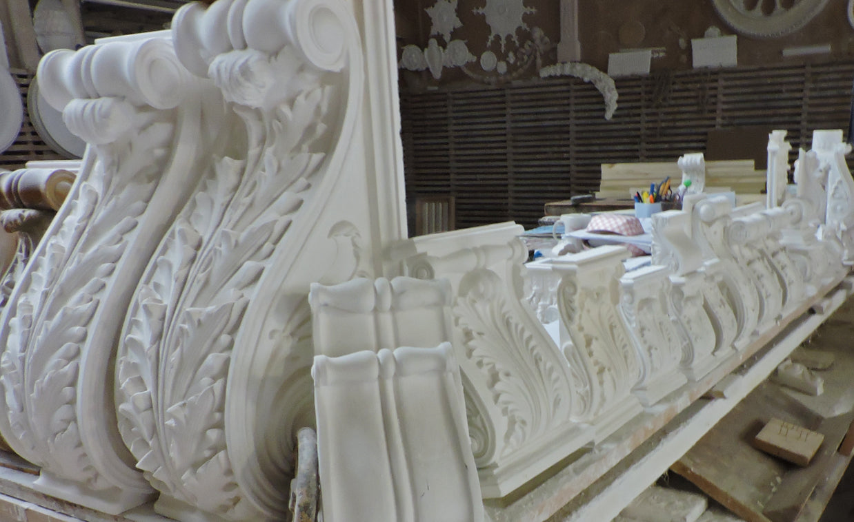 manufactured plaster corbel designs in a line sitting on a table