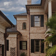 standard exterior architectural black paneled window shutters on a brick home