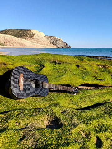 A KLOS travel guitar resting on the beach