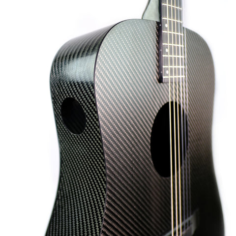 This picture shows a black carbon fiber guitar body with a traditional soundhole as well as a second 1 3/4 inch soundhole in the side of the upper lobe of the guitar's body.