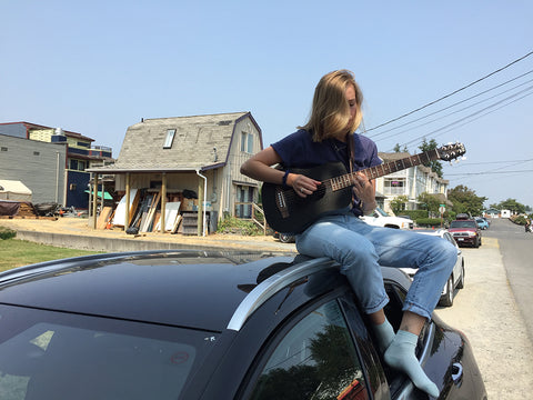 Girl playing guitar on top of a car