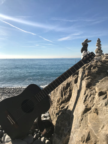 The KLOS travel guitar complemented by rock art.
