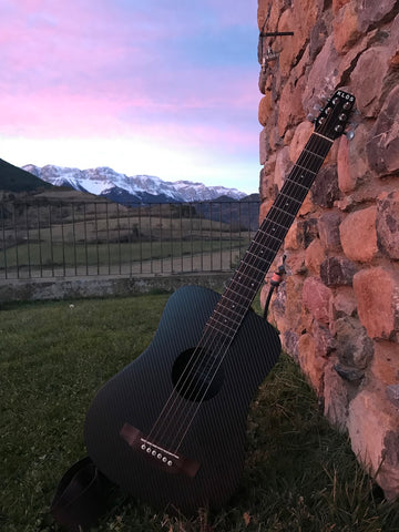 A KLOS travel guitar rests in the mountains.