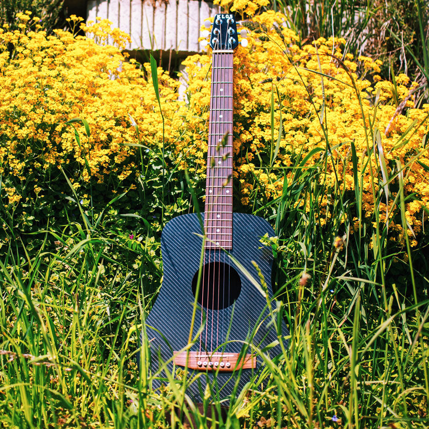 backpacker guitar sitting in the grass during a hike