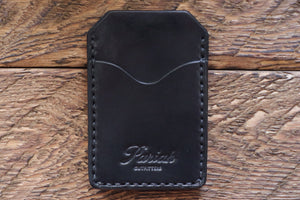 Black handmade and hand stitched money clip wallet on wood