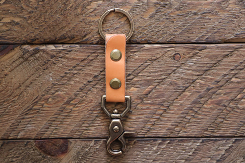 Russet handmade leather keychain with brass key ring and clip on wood