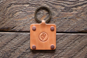 Russet handmade leather key fob with brass keyring and copper rivets on wood