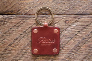 Brown handmade leather key fob with brass keyring and copper rivets on wood