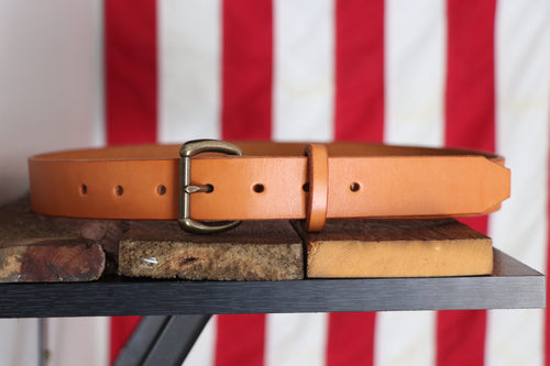 Tan leather belt with brass buckle on wood in front of American flag