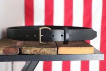 Black leather belt with brass buckle on wood in front of American flag