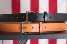 Black and Russet leather belts with brass buckles on wood in front of American flag