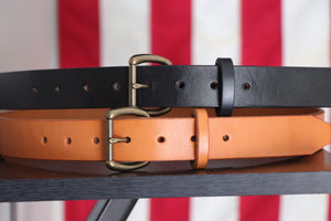 Black and tan leather belts with brass buckles on wood in front of American flag