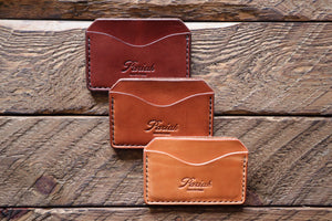 Brown handmade and hand stitched horizontal card case wallets on wood