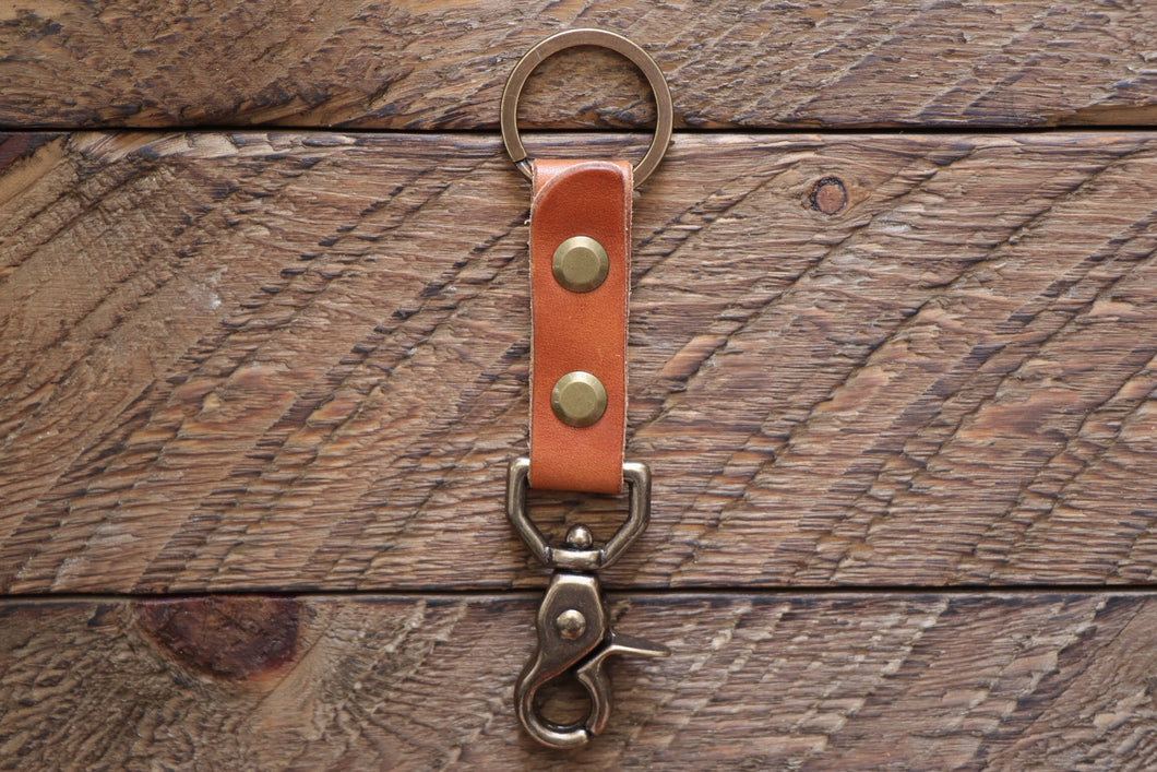 Brown handmade leather keychain with brass key ring and clip on wood