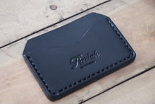 Black handmade and hand stitched horizontal card case wallet on wood