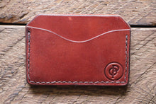 Brown handmade and hand stitched horizontal card case wallet on wood