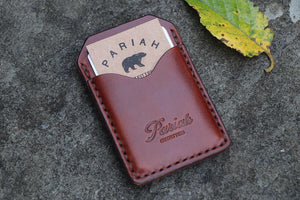 Brown handmade and hand stitched money clip wallet on slate with a leaf outside