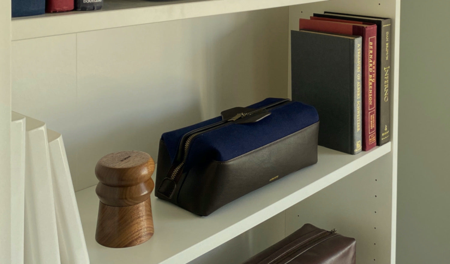 shelf with books, weed grinder and bag