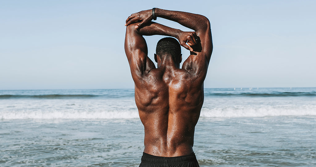 Picture of man flexing muscles  by sea