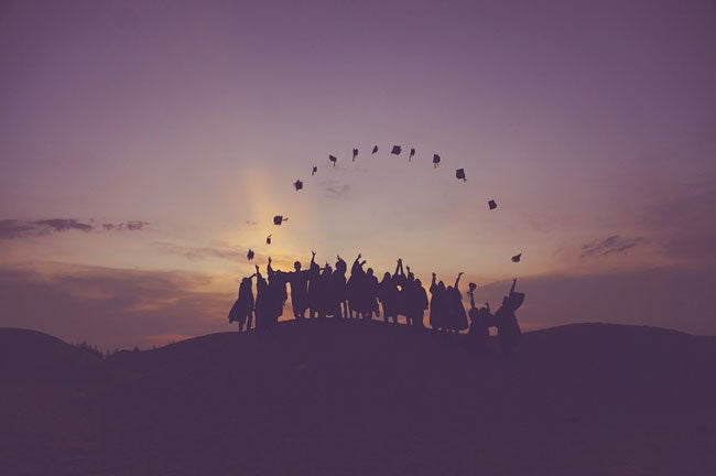 Graduates throwing their caps at sunset