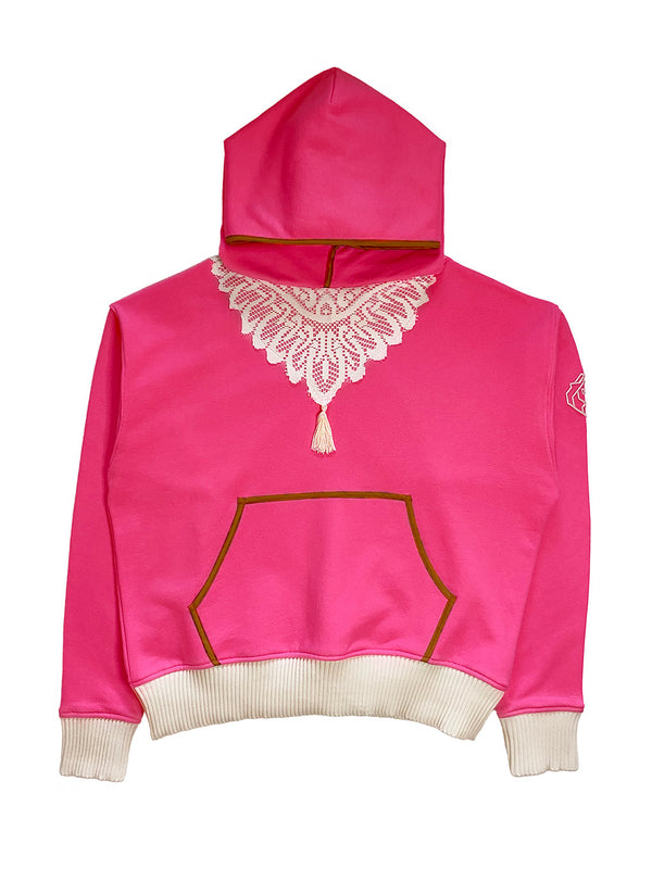 Front view of pink hoodie with doily motif on chest adorned with tassel. Cream color rib cuff and waist band. Khaki bias trim on hood edge and kangaroo pouch pocket edge.