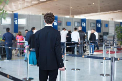 Back of a slim man with wavy brown hair wearing a navy suit and holding a suitcase looking at the airport security line.