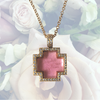 Delille Cross featuring a pink tourmaline and pave diamonds.