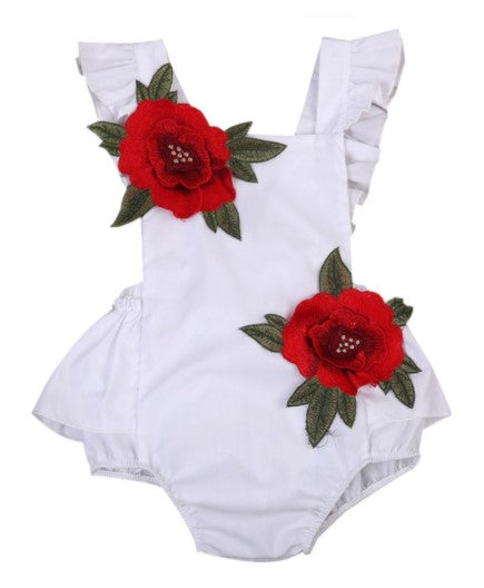 Adorable tie back floral romper. Hand stitched floral rosettes adorn the top and bottom (bottom of romper has snaps). Shoulders have ruffle edging and ties to a bow in the back.