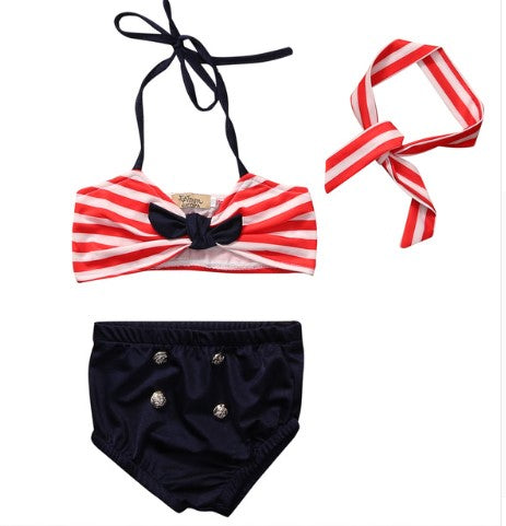 Blue bathing suit with 4 gold buttons, a red striped halter top and matching red stripe headband.