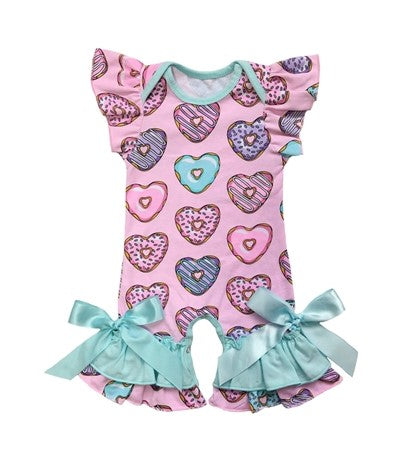 Baby pink romper with heart shaped donuts. The bottom of the romper has baby blue ribbon to tie into a bow