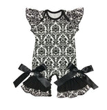 Damask pattern bell bottom romper with black Ribbon tied into bows at the bottom.
