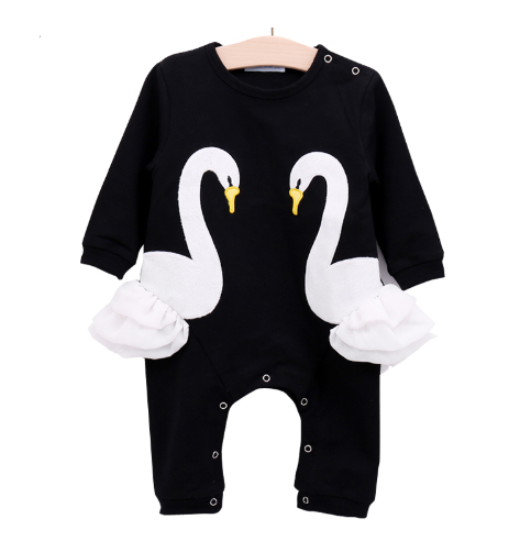 This black little girl's romper has two swans facing each other. The sides of the romper have white tulle that sticks out.