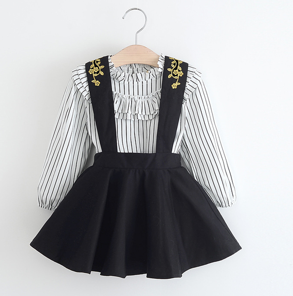 ruffled striped long sleeve shirt with black halter dress. Gold stitching lines the front and back of the straps.