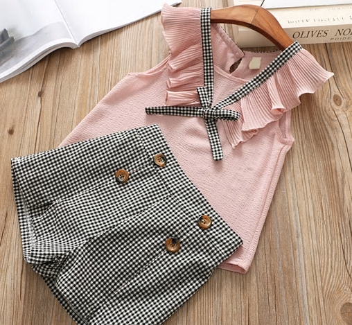 checkered shorts lined with two buttons on each side and flutter sleeveless pink top with extra sting to tie in a bow.