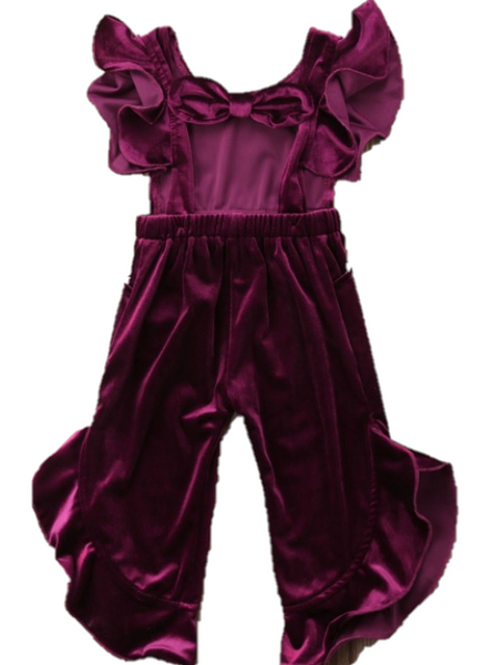 The sleeveless top has ruffles on the shoulders and the back is tied together in a bow. The pants have cascading ruffles lining both sides.