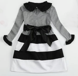Black, grey and white long sleeved dress with ruffle sleeaves and collar. A thick ribbon slides around the waist and ties in a big bow.