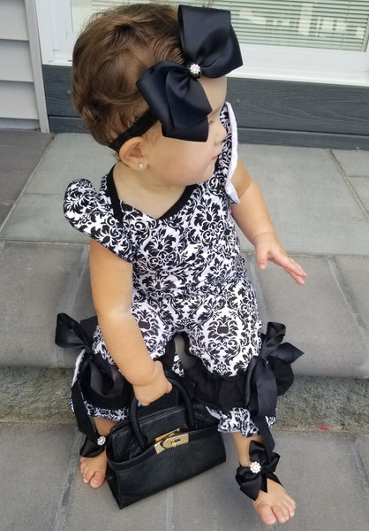 The Damask romper has fluttered sleeves and the ruffle bottom is ties with a black ribbon into a bow. Add on the accessories - Pictured is the black elastic headband (WITH BLING ADDED), the mini Birkin and our diamond toes on the feet!