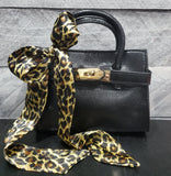 For our classic Boujie Fashionista's, our  Buckle Bag with Leopard Scarf completes all of our high fashion and dressy outfits. The bag comes with two handles along with a shoulder strap which hangs long on the side. There is a buckle in the front which clasps the bag together. Great accessory for babies, toddlers and tweens. The Leopard scarf can be removed.