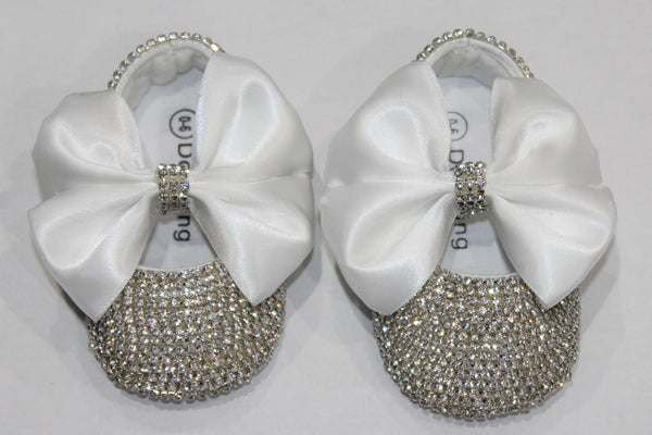 Entire shoe adorned with crystals. White Satin bow held together in middle with Crystal band.