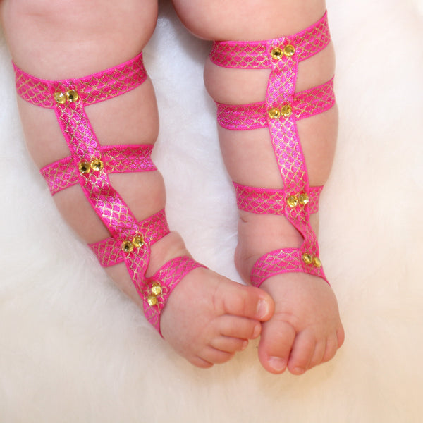 Hot pink barefoot children's gladiators have 8 gold crystals lining the fabric.