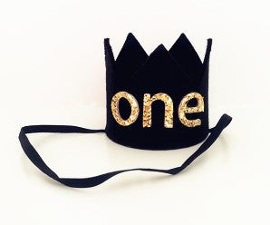 black crown with felt and the word ONE in gold glitter. There is an elastic band to keep headband on.
