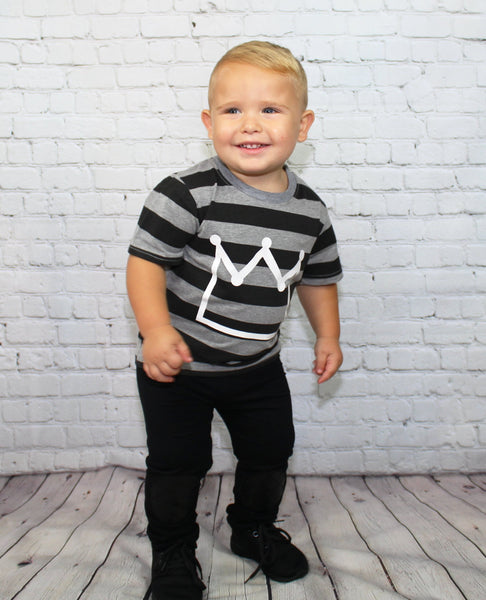 Toddler boy outfit comes with a grey and black striped t-shirt, a white crown symbol on the front and black pants with faux leather lining the knees.