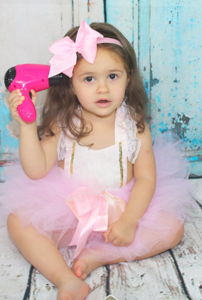 This 2 piece Princess Set is absolutely stunning! The pale pink tutu is super fluffy and ties with a pink and peach bow. The pink romper has a lace halter top that ties in the back. Lining the sides of the romper are gold sequins and lace. Your little girl will look adorable in her matching tutu set. This is great for birthday parties!
