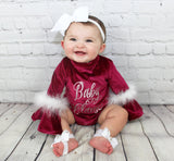 Get into the holiday spirit with this adorable red crushed velvet onesie. Each onesie has bell sleeves with white fur and the front says,
