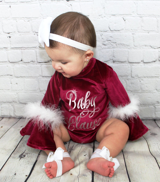 "Get into the holiday spirit with this adorable red crushed velvet onesie. Each onesie has bell sleeves with white fur and the front says, ""Baby Clause"" in a pretty silver stitch. This is a perfect outfit for your little diva to take holiday pictures in or to change into after wearing her Christmas dress. Check out our socks in accessories to complete the look"