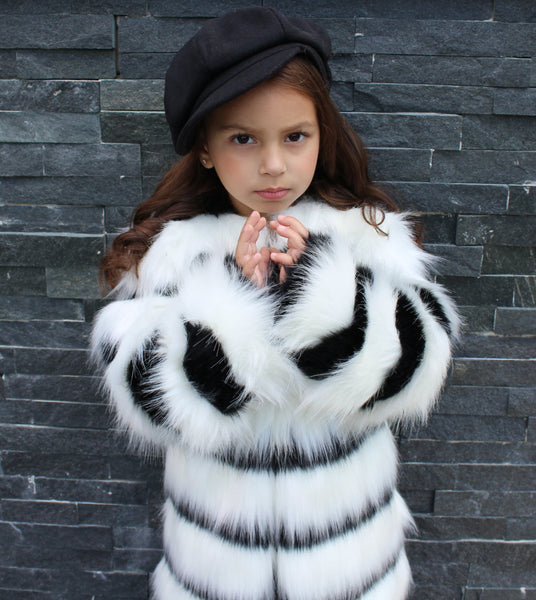 This black & white faux fur jacket is for the glamorous diva! This jacket will leave your mini fashionista nice and warm during the winter season. Add this to any of our Fall collections to complete the look.