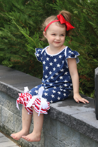 Bell bottom romper with the American flag pattern. White ribbon is tied into a bow at the bottom.